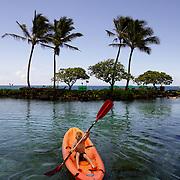 A young boy enjoys kayaking a saltwater lagoon on Kauai.