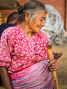 04 AUGUST 2015 - BUNGAMATI, NEPAL: A woman whose home was destroyed in the earthquake in the town square in Bungamati, a village about an hour from Kathmandu. Three months after the earthquake many families still live in tents and temporary shelters scattered around the village. The Nepal Earthquake on April 25, 2015, (also known as the Gorkha earthquake) killed more than 9,000 people and injured more than 23,000. It had a magnitude of 7.8. The epicenter was east of the district of Lamjung, and its hypocenter was at a depth of approximately 15 km (9.3 mi). It was the worst natural disaster to strike Nepal since the 1934 Nepal–Bihar earthquake. The earthquake triggered an avalanche on Mount Everest, killing at least 19. The earthquake also set off an avalanche in the Langtang valley, where 250 people were reported missing. Hundreds of thousands of people were made homeless with entire villages flattened across many districts of the country. Centuries-old buildings were destroyed at UNESCO World Heritage sites in the Kathmandu Valley, including some at the Kathmandu Durbar Square, the Patan Durbar Squar, the Bhaktapur Durbar Square, the Changu Narayan Temple and the Swayambhunath Stupa. Geophysicists and other experts had warned for decades that Nepal was vulnerable to a deadly earthquake, particularly because of its geology, urbanization, and architecture.    PHOTO BY JACK KURTZ