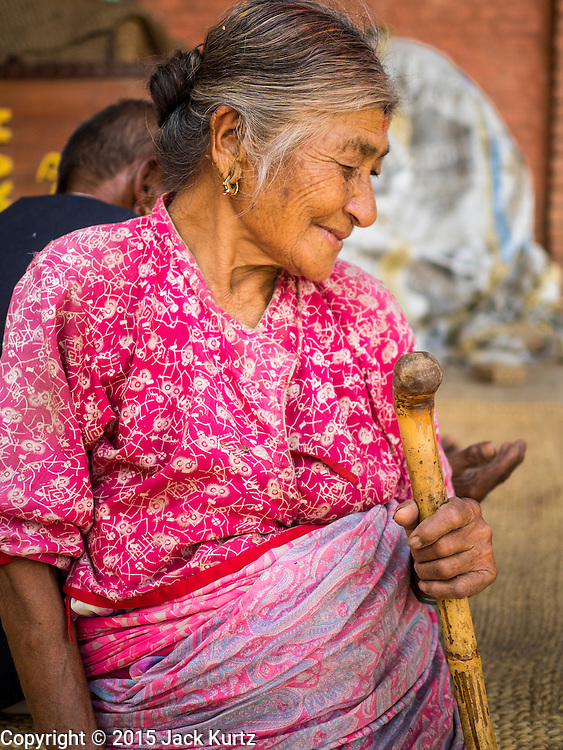 04 AUGUST 2015 - BUNGAMATI, NEPAL: A woman whose home was destroyed in the earthquake in the town square in Bungamati, a village about an hour from Kathmandu. Three months after the earthquake many families still live in tents and temporary shelters scattered around the village. The Nepal Earthquake on April 25, 2015, (also known as the Gorkha earthquake) killed more than 9,000 people and injured more than 23,000. It had a magnitude of 7.8. The epicenter was east of the district of Lamjung, and its hypocenter was at a depth of approximately 15km (9.3mi). It was the worst natural disaster to strike Nepal since the 1934 Nepal–Bihar earthquake. The earthquake triggered an avalanche on Mount Everest, killing at least 19. The earthquake also set off an avalanche in the Langtang valley, where 250 people were reported missing. Hundreds of thousands of people were made homeless with entire villages flattened across many districts of the country. Centuries-old buildings were destroyed at UNESCO World Heritage sites in the Kathmandu Valley, including some at the Kathmandu Durbar Square, the Patan Durbar Squar, the Bhaktapur Durbar Square, the Changu Narayan Temple and the Swayambhunath Stupa. Geophysicists and other experts had warned for decades that Nepal was vulnerable to a deadly earthquake, particularly because of its geology, urbanization, and architecture.    PHOTO BY JACK KURTZ