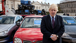 © Licensed to London News Pictures. 19/10/2011. LONDON, UK. The Mayor of London, Boris Johnson, stands in front of seized cars on Horse Guards Parade in London today (19/10/11).  The cars were all seized as part of 'Operation Reclaim', a coordinated Metropolitan Police operation across the capital cracking down on uninsured drivers. Photo credit: Matt Cetti-Roberts/LNP