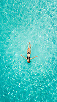 Aerial view of a woman floating in the sea of Ithaca island.