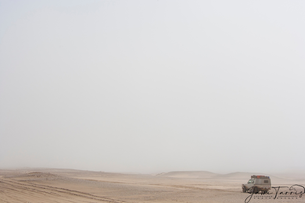 A single vehicle parked in the desert along the Skeleton Coast in the fog ,Skeleton Coast, Namibia, Africa
