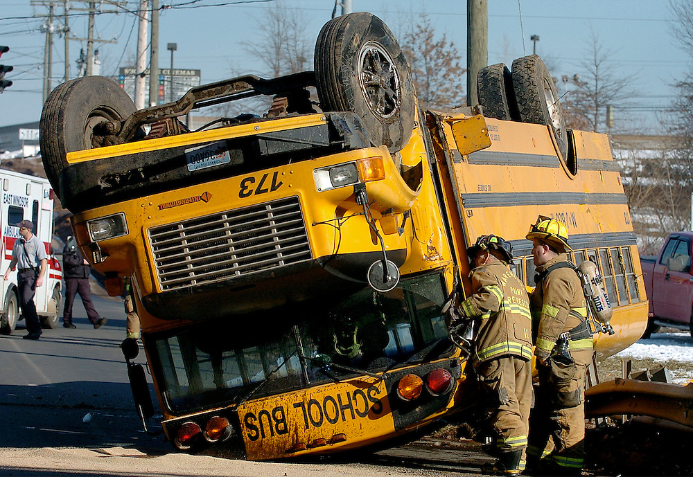 Firefighters examine a school bus that turned over onto Bridge St. in East Windsor, Conn.
