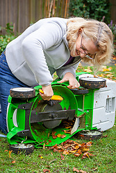 Cleaning a mower with a hand brush before storing over winter