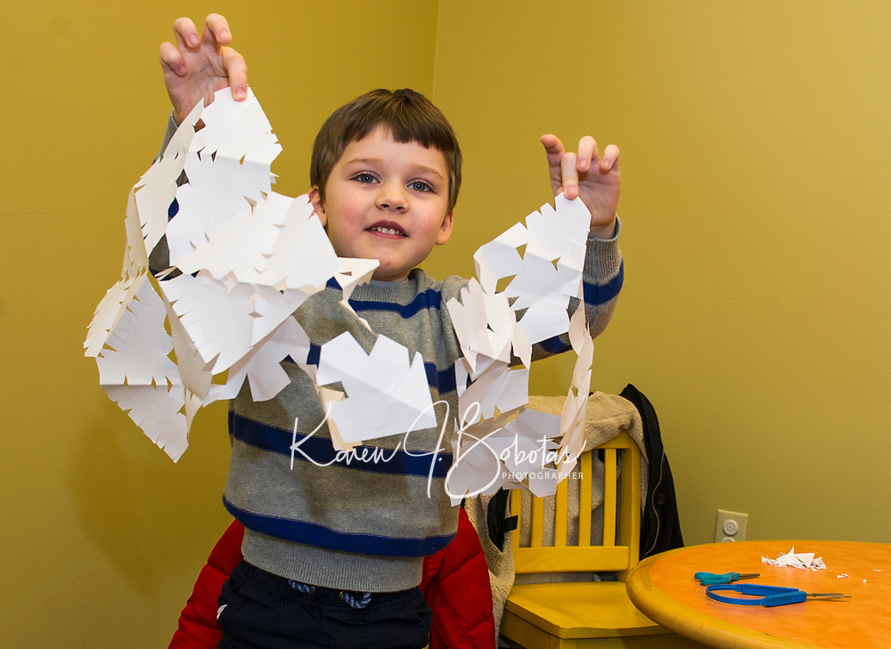 """Luke Dorval-Drown shows off the snowflakes he made after reading """"Snowmen At Night"""" during Laconia Library's preschool story hour on Wednesday morning.  (Karen Bobotas/for the Laconia Daily Sun)"""