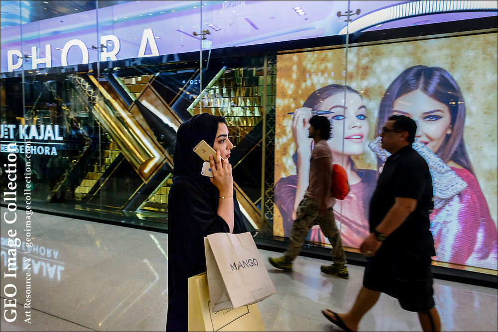 Holding two mobile telephones, an Arab woman talks on her phone inside Dubai Mall, largest shopping complex in the world.