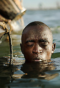 A sand diver shivers from the cold and takes a breath before diving back down to the bottom of the Niger River at Segou, Mali. People dive to the bottom of the river, filling buckets with sand to be used in construction all over the country. Many people die each year doing this dangerous job