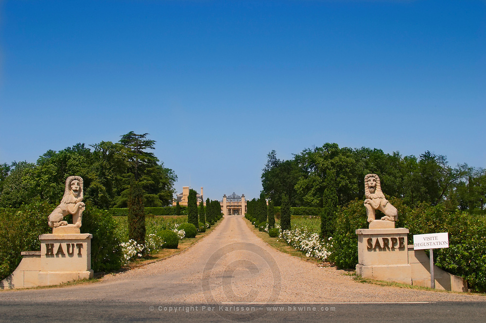 The imposing entrance to Chateau Haut Sarpe with two lion stone statues and a road lined with bushes leading up to the gate and a humble sign saying wine tastings and visits Saint Emilion Bordeaux Gironde Aquitaine France