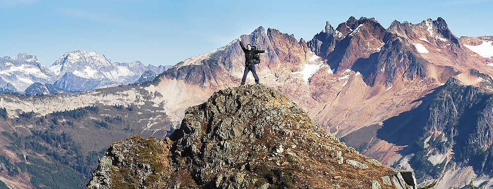 A young woman stands, arms raised, on a high ridge near Hurricane Peak in Glacier Peak Wilderness, Washington. The crags of the Buckindy Group are visible beyond.