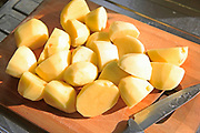 Peeled cut chopped potatoes on chopping board with kitchen knife