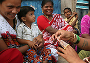 Surekha Kamble demonstrates how to use a condom to other sexworkers in Miraj's redlight district where lives and works as a Devadasi sexworker. While Kamble has been a Devadasi sexworker since she was sixteen, she is also a peer educator involved in raising awareness in her community about HIV/AIDS as well as other sexually transmitted diseases.  Her two daughters, Chandrike and Ropani, are both being educated at a residential school for the children of Devadasis and she has hopes that they will not follow her into the Devadasi lifestyle.