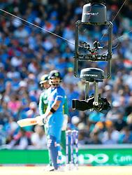 The obtrusive Spider Cam TV camera, low over the pitch &  Virat Kohli (capt.) of India