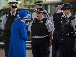 Queen Elizabeth II speaks to emergency services personnel as she arrives to meet members of the community affected by the fire at Grenfell Tower in west London during a visit to the Westway Sports Centre which is providing temporary shelter for those who have been made homeless in the disaster.