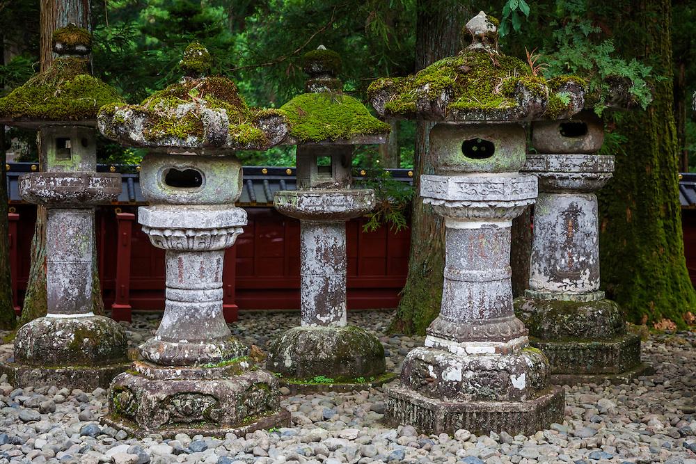 JAPAN, NIKKO - August 2012 - Stone lamp in the Toshogu Shrine is where the famous Shogun of the Edo Period in the 17th century, Tokugawa Ieyasu, was worshiped after his death. It became as luxurious and elaborate as it looks today when the grandson of Ieyasu, the third Shogun Tokugawa Iemitsu, reconstructed it. The engravings on the Yomei-mon Gate are especially overwhelming, provided with every luxury imaginable and redolent in gorgeous colors. site calssified as Japanese Cultural property and world heritage by UNESCO [FR] Lampe de pierre Sanctuaire Toshogu - Construit en 1636 à la mémoire de Ieyasu, fondateur du shogunat Tokugawa. Contrairement aux autres sanctuaires shinto, caractérisés par une architecture épurée se fondant dans le paysage environnant, ce sanctuaire est une exubérance de couleurs, d'applications de feuilles d'or et de sculptures en tous genres.Site classé propriete culturelle du Japon et patrimoine mondial de l'UNESCO