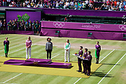Crowds watch in Centre Court as the Tennis events at the London 2012 Olympics take place at Wimbledon. Serena Williams awaits her gold medal during the medal ceremony.