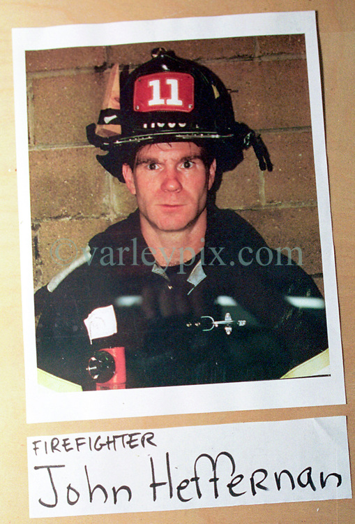 14 September 2001. New York, New York - USA.<br /> Post 9/11 World Trade Center attack.<br /> John Heffernan, firefighters. Missing presumed dead. Hero firefighter, colleagues of Mike Kehoe of Engine 28, Ladder 11 pictured in a memorial erected at their firehouse on East 2nd Street in the East village early in the morning of Sept 14th. <br /> Mike Kehoe's image had been published the day before on front pages around the world. It is the iconic image of him ascending the stairs of the World Trade Center as he helped to evacuate people from the terrorist attacks of 9/11. It was assumed Mike had perished when the buildings collapsed. However Mike had miraculously managed to escape the buildings moments before they collapsed. 6 members of his crew were not so fortunate. Mike became a symbol of heroism to many following the vicious Al Queda attacks which claimed over 2,000 victims at the WTC site. This images was published exclusively on the Front Page of the Daily Mirror on 15th Sept, 2001.<br /> Photo exclusive©; Charlie Varley/varleypix.com