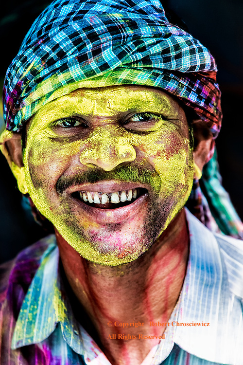 This portrait shows a laughing young man with a face plastered with yellow powder, celebrating Holi in Kolkata (Calcutta) India.