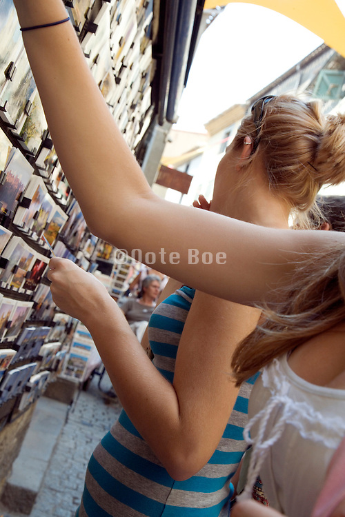 young female tourists looking for postcards in side La Cite Carcassonne