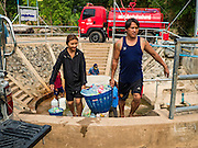 10 MAY 2016 - TA TUM, SURIN, THAILAND: People carry water from the artesian well in Ta Tum, Surin, Thailand back to their pickup truck. They filled hundreds of recycled soft drink bottles with water from the well. The well is the most important source of drinking water for thousands of people in the communities surrounding it. In the past many of the people had domestic water piped to their homes or from wells in their villages but those water sources have dried up because of the drought in Thailand. Thailand is in the midst of its worst drought in more than 50 years. The government has asked farmers to delay planting their rice until the rains start, which is expected to be in June. The drought is expected to cut Thai rice production and limit exports of Thai rice. The drought, caused by a very strong El Nino weather pattern is cutting production in the world's top three rice exporting countries:  India, Thailand and Vietnam. Rice prices in markets in Thailand and neighboring Cambodia are starting to creep up.   PHOTO BY JACK KURTZ