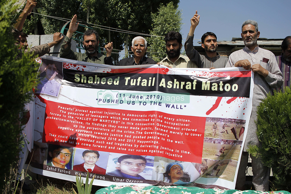 June 11, 2017 - Srinagar, Jammu and Kashmir, India - Family members and the pro-independence group leaders hold a banner as they shout pro-freedom slogans  in front of the Grave of Tufail Matoo 17 year old school boy on his 7th death Anniversary at the Martyrs graveyard in Srinagar on June 11,2017.Tufail Matoo 17 year old school boy,who was allegedly killed by indian police on june 11 2010 when he was returing from tutions and a tear smoke shell hit his head and dies on the spot,Tufail's Killing sparked a new wave of Anti-India protests in the kashmir region resulting in killing of more than 100 people in 2010. (Credit Image: © Syed Shahriyar/NurPhoto via ZUMA Press)