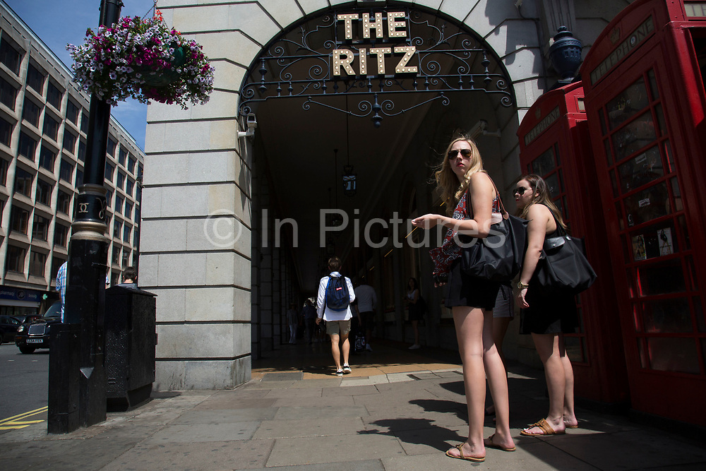 Summertime in London, England, UK. Tourists pass by via the arched walkway to the famous Ritz Hotel on Piccadilly, Mayfair. The Ritz, London is a Grade II listed 5-star hotel located in Piccadilly in London, England. A symbol of high society and luxury, the hotel is one of the world's most prestigious and best known hotels.