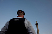Seen from behind and from a low angle, we see the towering, imposing figure of a City of London Police officer while on duty in Trafalgar Square during England v USA World Cup match. At the half-time pause in the game, the officer stands to watch over this location noted for political protest and sporting celebrations. On this occasion though, there is no large TV screen to avoid social disorder and the City of London Police who usually patrol the capital's old financial district are helping the larger Met Police force during this sporting summer. Seemingly below him, is the 5.5 m (18 ft) statue of Admiral Nelson on its 46 m (151 ft) Foggintor granite column, built between 1840 and 1843 to commemorate the heroic Napoleonic war sailor Horatio Nelson's death at the Battle of Trafalgar in 1805.