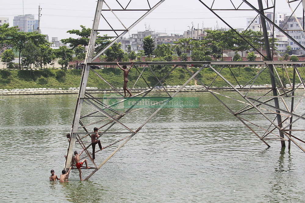 May 5, 2017 - Dhaka, Bangladesh - On the hot summer noon, Bangladeshi children climb on a electricity supply tower to jump in the water as they play and take bathe in the polluted water of Hatirjheel lake at Dhaka, Bangladesh, May 5, 2017. The continued release of untreated sewage into the Hatirjheel pose serious heath hazards to all the residents of the crowded localities surrounding the city's showcase lake. (Credit Image: © Suvra Kanti Das via ZUMA Wire)