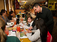 Kendra and Eli practice their Spanish as they order lunch with server Antonio Leon at the Restaurante El Jimador on Wednesday afternoon with Mrs. McKinney and fellow 4th and 5th graders from Holy Trinity School.  (Karen Bobotas/for the Laconia Daily Sun)