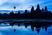 "02 JULY 2013 - ANGKOR WAT, SIEM REAP, SIEM REAP, CAMBODIA:  The west side of Angkor Wat is silhouetted by the rising sun. Angkor Wat is the largest temple complex in the world. The temple was built by the Khmer King Suryavarman II in the early 12th century in Yasodharapura (present-day Angkor), the capital of the Khmer Empire, as his state temple and eventual mausoleum. Angkor Wat was dedicated to Vishnu. It is the best-preserved temple at the site, and has remained a religious centre since its foundation – first Hindu, then Buddhist. The temple is at the top of the high classical style of Khmer architecture. It is a symbol of Cambodia, appearing on the national flag, and it is the country's prime attraction for visitors. The temple is admired for the architecture, the extensive bas-reliefs, and for the numerous devatas adorning its walls. The modern name, Angkor Wat, means ""Temple City"" or ""City of Temples"" in Khmer; Angkor, meaning ""city"" or ""capital city"", is a vernacular form of the word nokor, which comes from the Sanskrit word nagara. Wat is the Khmer word for ""temple grounds"", derived from the Pali word ""vatta."" Prior to this time the temple was known as Preah Pisnulok, after the posthumous title of its founder. It is also the name of complex of temples, which includes Bayon and Preah Khan, in the vicinity. It is by far the most visited tourist attraction in Cambodia. More than half of all tourists to Cambodia visit Angkor.         PHOTO BY JACK KURTZ"