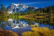 """Mount Shuksan in Washington state's North Cascades National Park reflecting in Picture Lake. Mount Shuksan is a glaciated massif in the North Cascades National Park. Shuksan rises in Whatcom County, Washington immediately to the east of Mount Baker, and 11.6 miles  south of the Canadian border. The mountain's name Shuksan is derived from the Lummi word, said to mean """"high peak"""". The highest point on the mountain is a three sided peak known as Summit Pyramid. There are two named subsidiary peaks: Nooksack Tower and The Hourglass. The mountain is composed of Shuksan greenschist, oceanic basalt that was metamorphosed when the Easton terrane collided with the west coast of North America, approximately 120 million years ago. The mountain is an eroded remnant of a thrust plate formed by the Easton collision."""