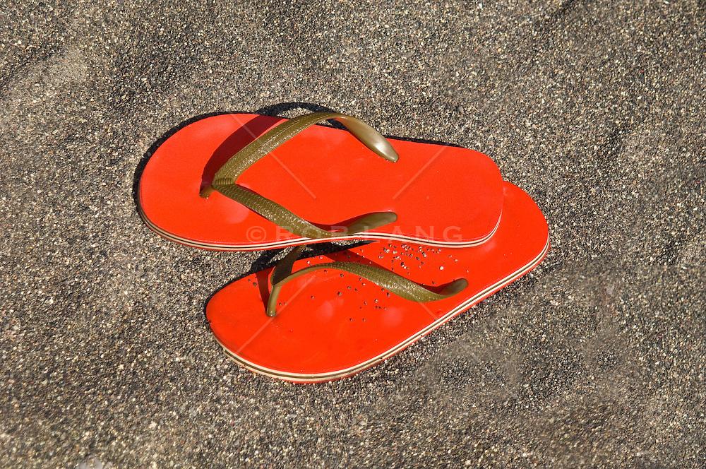 Pair Of Red Flip Flops Sandals On Black Sand Beach