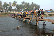 A crowd of people cross a rustic bamboo bridge over the Nam Hung river in Sayaboury to attend the Sayaboury elephant festival, Sayaboury province, Lao PDR.