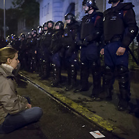 Demonstrator sits on the street in front of a line of riot police during a protest against the planned Internet tax in Budapest, Hungary on October 26, 2014. ATTILA VOLGYI