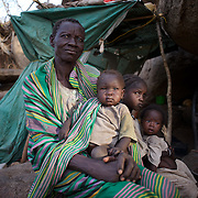 April 28, 2012 - Buram, Nuba Mountains, South Kordofan, Sudan: A Nuba family seats under the shade of a tree near their improvised home in the mountains outside Buram village in South Kordofan's Nuba Mountains...Since the 6th of June 2011, the Sudan's Army Forces (SAF) initiated, under direct orders from President Bashir, an attack campaign against civil areas throughout the South Kordofan's province. Hundreds have been killed and many more injured...Local residents, of Nuba origin, have since lived in fear and the majority moved from their homes to caves in the nearby mountains. Others chose to find refuge in South Sudan, driven by the lack of food cause by the agriculture production halt due to the constant bombardments of rural areas. (Paulo Nunes dos Santos/Polaris)