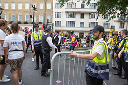 London, UK. 6 July, 2019. Pride in London stewards try to prevent activists from Lesbians and Gays Support The Migrants, African Rainbow Family, the Outside Project, Micro Rainbow and other LGBT+ groups from joining the Pride in London parade in solidarity with those for whom Pride in London is inaccessible and in protest against the corporatisation of Pride in London. A police officer asks the stewards to remove barriers which they had placed in their way.