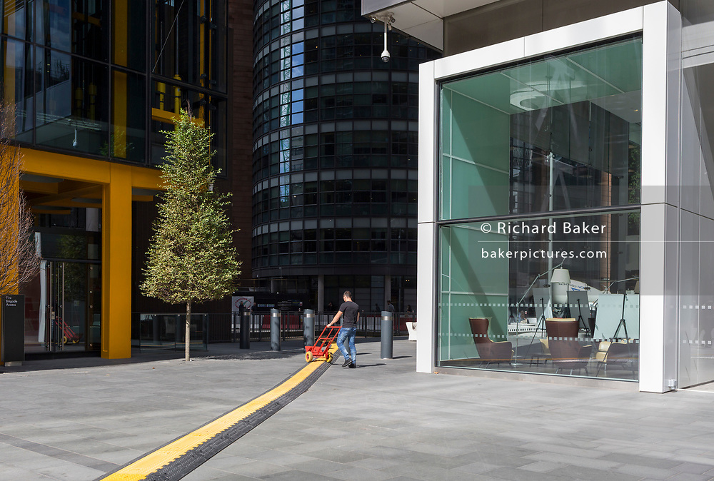 A delivery man pushes a trolley alongside a yellow line covering hazardous electrical cabling at Leadenhall in the City of London, (aka The Square Mile) the capital's financial district, on 2nd September 2019, in London, England.