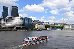 Tour boat on River Thames. In the background: City of London - 20 Fenchurch Street (Walkie Talkie building) and The Leadenhall Building (The Cheesegrater), London 2017