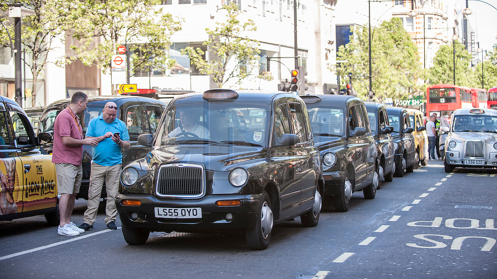 """© Licensed to London News Pictures. 21/04/2015. Oxford Street, London, UK. London black cab taxi drivers, members of the United Cabbies Group, take part in the """"Enough is Enough"""" protest bringing the normally busy Oxford Street to a standstill.  They were demonstrating against Transport for London, their regulator, for refusing to enforce their own regulations leaving Londoners' safety at risk.   Photo credit : Stephen Chung/LNP"""