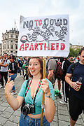 """London, United Kingdom, July 24, 2021: A young lady smiles as she holds a placard against Vaccine Passports in Trafalgar during an """"anti-Lockdown"""" demonstration in central London, on Saturday, July 24, 2021. (VX Photo/ Vudi Xhymshiti)"""