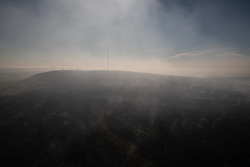 © Licensed to London News Pictures . 04/07/2018 . Bolton , UK . Free to use aerial photograph provided by the Woodland Trust showing the scarred landscape at Winter Hill and the iconic transmitter mast (the highest in England), as fire-fighters continue to work to control the spread of the blaze . The Woodland Trust estimates it has lost a fifth of the area it manages around Winter Hill , damaging precious moors and upland grassland , endangering the surrounding woods and wildlife and threatening people's homes . Photo credit: Joel Goodman/LNP