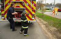 """Responding to his first fire Paul Swenson pulls out the fire hose with the help of Chad Vaillancourt during his """"Day as a Fireman"""" with Make A Wish on Sunday with the Laconia Fire Department.  (Karen Bobotas/for the Laconia Daily Sun)"""