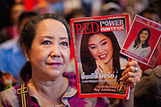 03 JULY 2011 - BANGKOK, THAILAND:   A woman in Bangkok holds up some of Yingluck Shinawatra's campaign literature after the Pheu Thai party and Yingluck Shinawatra won the Thai elections Sunday night. Yingluck Shinawatra and the Pheu Thai Party scored a massive landslide win in the Thai election Sunday. Pheu That is estimated to have won more than 300 seats in Thailand 500 seat parliament, so they won an absolute majority and could govern without having to form a coalition with minor parties. Pheu Thai is the latest incarnation of deposed former Prime Minister Thaksin Shinawatra's political party. Yingluck is his youngest sister. Many observers expect legal challenges to the Pheu Thai victory and the election does not completely resolve Thailand's difficult political history of the last five years.   PHOTO BY JACK KURTZ