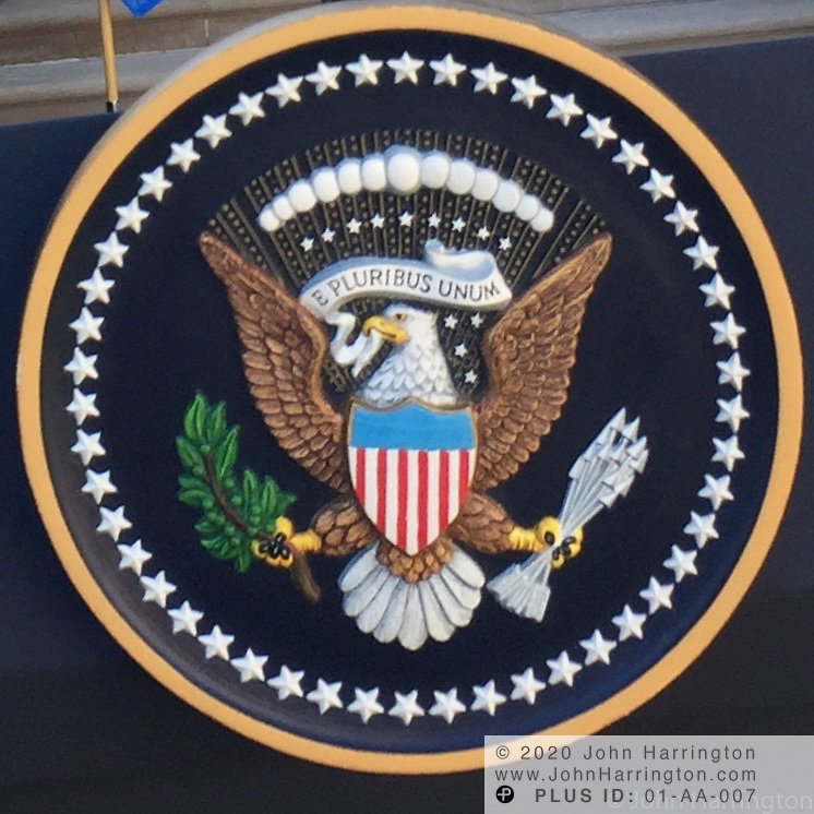 The Presidential Seal on a podium in the Rose Garden.