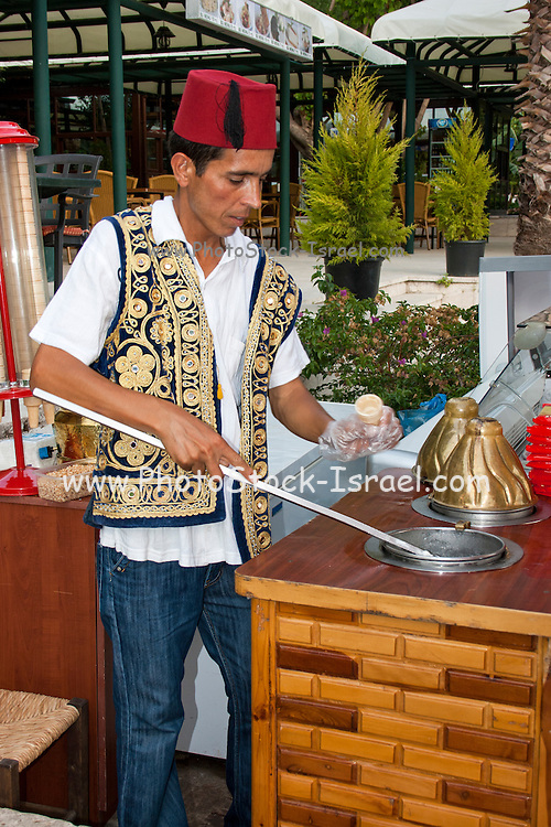Man in traditional clothes serves ice cream from a cart. Taurus Mountains, Turkey