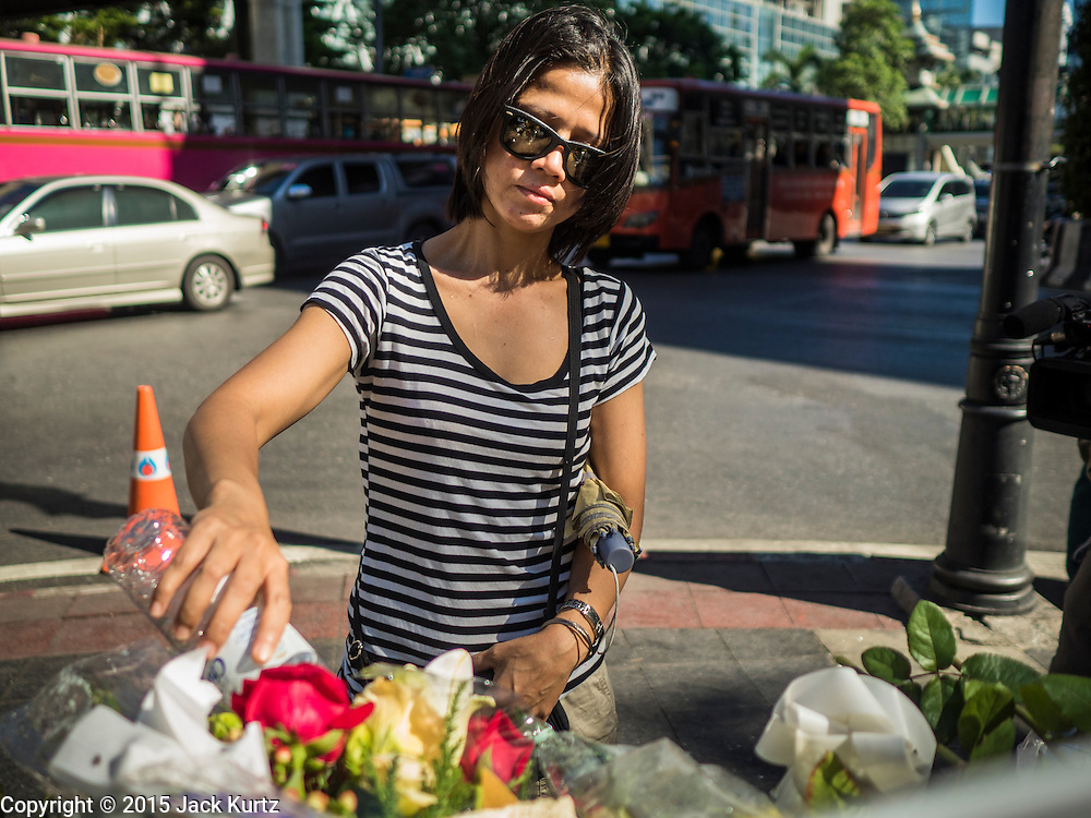 19 AUGUST 2015 - BANGKOK, THAILAND:  A woman leaves an offering at a memorial in front of Erawan Shrine during the reopening of the shrine. Erawan Shrine in Bangkok reopened Wednesday morning after more than 20 people were killed and more than 100 injured in a bombing at the shrine Monday, August 17, 2015. The shrine is a popular tourist attraction in the center of Bangkok's high end shopping district and is an important religious site for Thais. No one has claimed responsibility for the bombing.     PHOTO BY JACK KURTZ