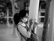 """14 JANUARY 2019 - BANGKOK, THAILAND:      A woman wearing a dust filter breathig mask photographs the Bangkok skyline with her smartphone. Bangkok has been blanketed by heavily polluted air for almost a week. Monday morning, the AQI (Air Quality Index) for Bangkok  was 182, worse than New Delhi, Jakarta, or Beijing. The Saphan Kwai neighborhood of Bangkok recorded an AQI of 370 and the Lat Yao neighborhood recorded an AQI of 403. An AQI above 50 is considered unsafe. Public health officials have warned people to avoid """"unnecessary"""" outdoor activities and wear breathing masks to filter out the dust.   PHOTO BY JACK KURTZ"""