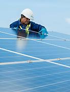 Photographie couleur d'un technicien Enercal contrôlant un panneau photovoltaïque. Photothèque d'Enercal.