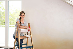 Woman alone working decorating painting ladder
