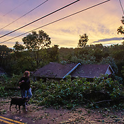 Rachel Trout walks her dog Lilly past a house partly destroyed by a falling tree after a tornado tore through Charleston, W.V., on June 24, 2019.