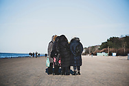 Jurmala, Latvia - March 15, 2020: A group of women stand in a huddle and talk together on Dzintari Beach in the Latvian resort city of Jūrmala.
